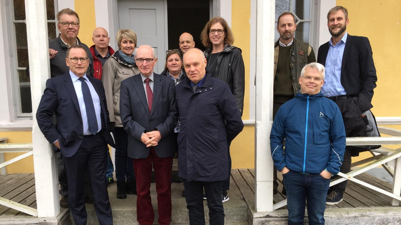 Landshövding Tomas Carlzon, tjänstemän från länsstyrelsen, markägarna och representanter från Södra och LRF står på trappan och verandan till det gula boningshuset på Värnanäs.