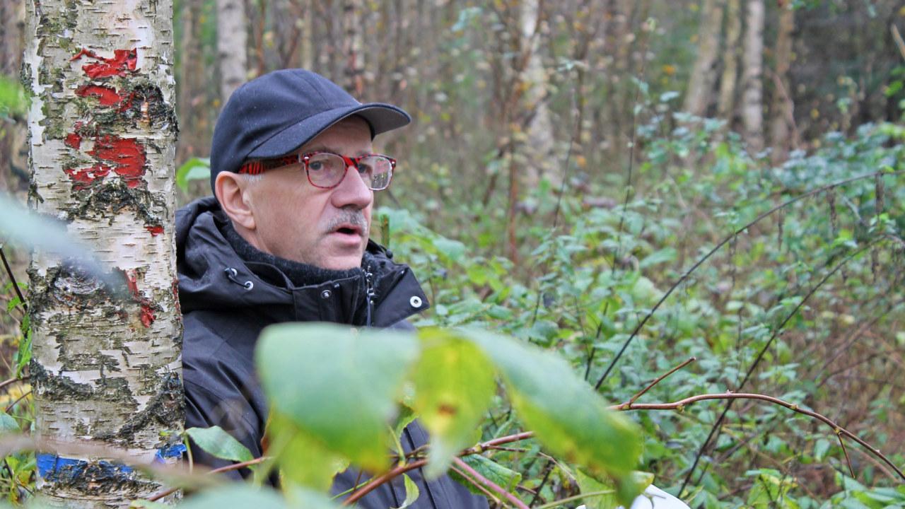 Jens Peter Skovsgaard ute i björkskog. Blå jacka, blå keps, röda glasögon och grå mustasch. Gröna löv i förgrunden.